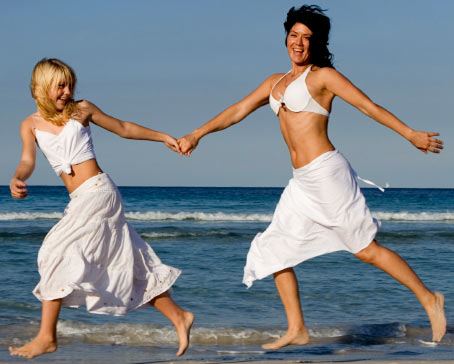 Mother and daughter playing happily on the beach, floating on air - OTC hemroids treatments can help you do this as well.