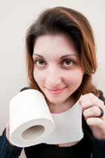 Woman holding hard toilet paper - hard toilet paper can cause hemorrhoids and scratch and abrade existing hemorrhoids.